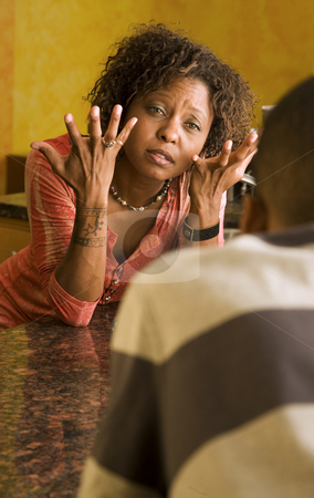 African-American female and male talk in kitchen stock photo, Upset African-American woman talking with a male family member in kitchen setting by Scott Griessel