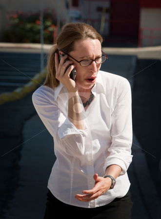 Shocked and amazed woman talks on cell phone stock photo, Shocked young woman is amazed at what she is hearing. by Scott Griessel