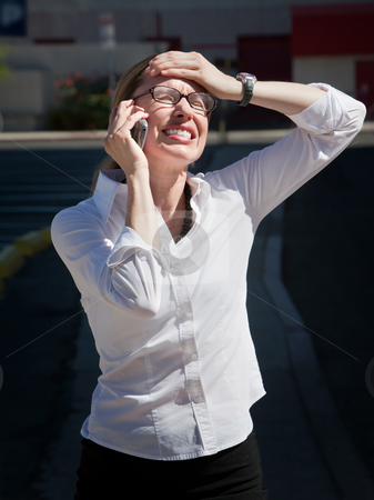 Pretty exasperated woman talks on cell phone stock photo, Shocked young woman is amazed at what she is hearing. by Scott Griessel