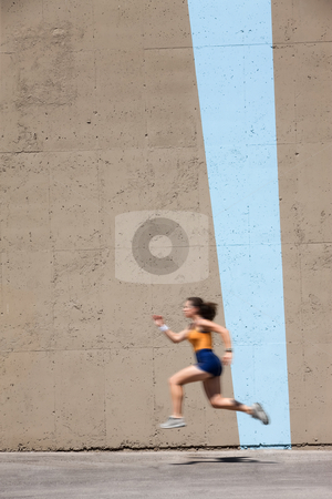 Muscular woman sprints to win stock photo, Woman sprinter practices her dash to the finish line. by Scott Griessel