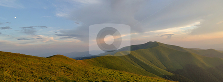 Light blue evening sky above grassy mountain ridge panorama stock photo,  by fotosutra