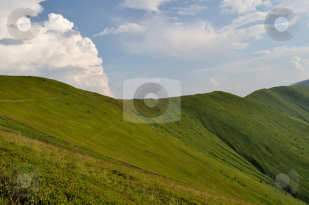 Mountain ridge slopes covered by green grass and cloudy blue sky stock photo,  by fotosutra