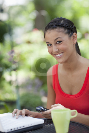 Beautiful Young Woman Using a Cellphone and Laptop Outdoors stock photo, Young Asian woman sits at an outdoor mesh table with a laptop, mobile phone and coffee cup. She is smiling at the camera. Vertical shot. by Edward Bock