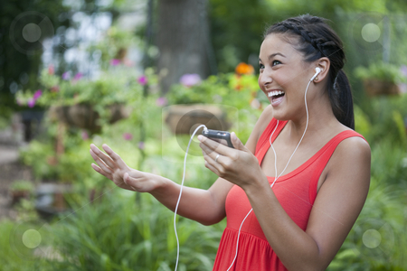 Cute Young Woman Dancing to Music Outdoors stock photo, Attractive young Asian woman playfully dances to music on her portable music device. Horizontal shot. by Edward Bock