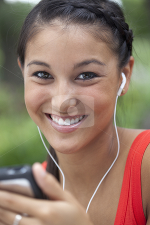 Cute Young Woman Using an MP3 Player stock photo, Beautiful Asian woman listens to music on a portable player. She is smiling into the camera outdoors. Vertical shot. by Edward Bock