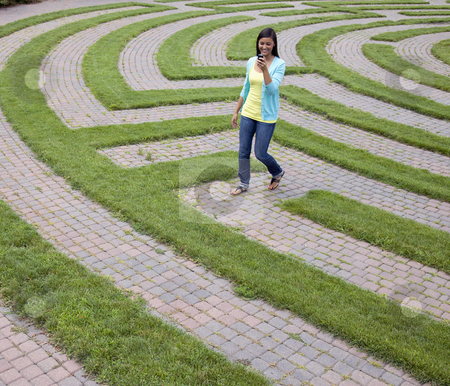 Young Woman Walking Through a Maze With Her Cellphone stock photo, Beautiful young Asian woman smiles while reading her mobile phone and walking through a maze. Square shot. by Edward Bock