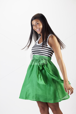 Attractive Young Woman in a Green Skirt stock photo, Beautiful young Asian woman models a green skirt. She is smiling towards the camera and has her hair in motion. Vertical shot. by Edward Bock