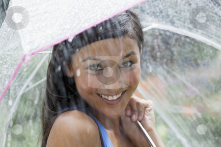 Young Woman Using an Umbrella in Rain stock photo, Beautiful young woman smiles towards the camera while holding an umbrella under a spray of water. Horizontal shot. by Edward Bock