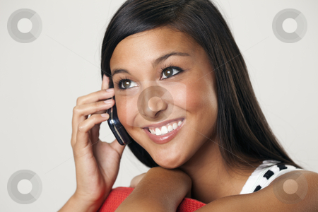 Beautiful Young Woman on a Cellphone stock photo, Attractive young Asian woman smiles while holding a mobile phone to her ear. Horizontal shot. by Edward Bock