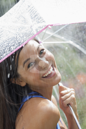 Young Woman Using an Umbrella in Rain stock photo, Beautiful young woman smiles towards the camera while holding an umbrella under a spray of water. Vertical shot. by Edward Bock