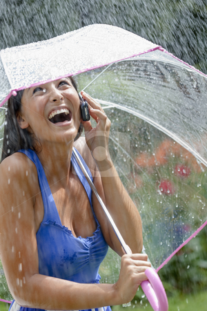 Young Woman Using a Cellphone and Umbrella in Rain stock photo, Attractive young woman laughs while talking in the phone in a rainstorm. She is holding a clear umbrella over her head. Vertical shot. by Edward Bock