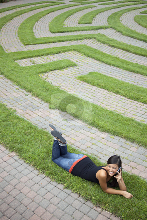 Young Woman Talking on the Phone in a Grass Maze stock photo, Beautiful young Asian woman lies down on the grass of a park labyrinth while enjoying a conversation on her cellphone. Vertical shot. by Edward Bock