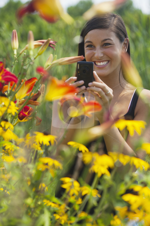Beautiful Young Woman Photographing Flowers stock photo, Cute Asian woman smiles while taking pictures of flowers with a small camera. Vertical shot. by Edward Bock