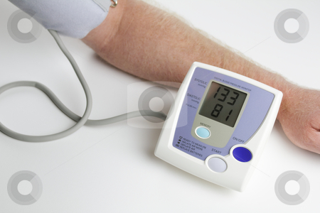 Blood pressure monitoring stock photo, Man measuring his own blood pressure by Lee Serenethos
