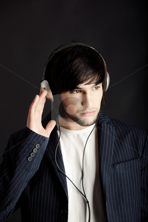 Listening stock photo, Young Man listening to music with headphones by ikostudio