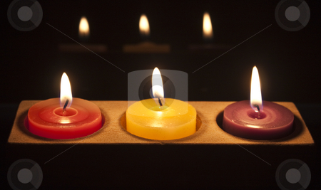 Red, yellow and purple candles in a row stock photo, A row of candles growing in the dark by Stephen Clarke