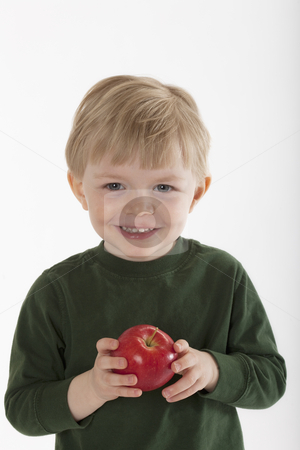 Young Boy Holding an Apple stock photo, Little boy smiles at the camera while holding an apple in his hands. Vertical shot. by Edward Bock