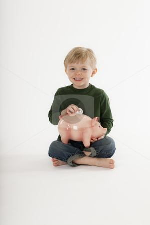 Young Boy Saving Money in a Coin Bank stock photo, Cute little boy sits cross-legged on the floor and smiles at the camera while inserting a coin into a piggy bank. Vertical shot. by Edward Bock