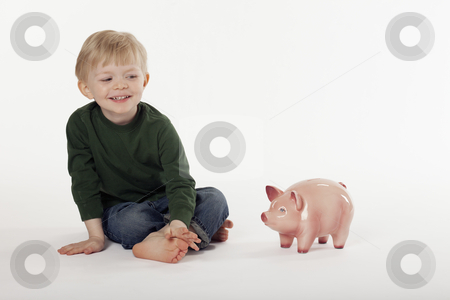 Young Boy and a Piggy Bank on the Floor stock photo, Cute little boy sits cross-legged next to a piggy bank on the floor. Horizontal shot. by Edward Bock