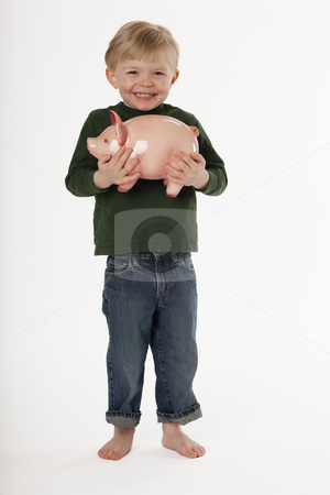 Little Boy Holding a Piggy Bank stock photo, A young, barefoot boy is standing and smiling while holding a piggy bank. Vertical shot. by Edward Bock