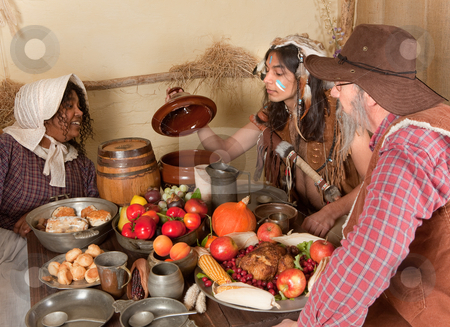 Thanksgiving pilgrim dinner stock photo, Reenactment scene of the first Thanksgiving Dinner in Plymouth in 1621 with a Pilgrim family and a Wampanoag Indian by Anneke