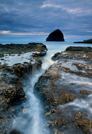 Splitting Stone stock photo, Rising tides surge through a crevice in the barnacle covered rocks at Cape Kiwanda on the Oregon Coast by Mike Dawson