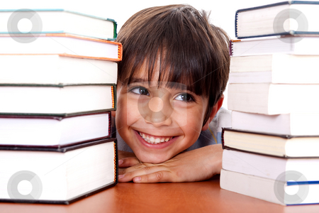 Young kid relaxing between pile of books stock photo, Young kid relaxing between pile of books and looking away by Get4net 