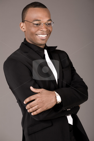 Happy young african business man laughing stock photo, Happy young african business man laughing on a grey background by Get4net
