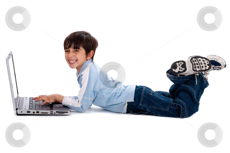 Young boy surfing on his laptop stock photo, Young boy lying on floor and surfing on his laptop by Get4net 