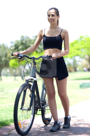 Young fitness woman with bicycle stock photo, Young fit and healthy woman with bicycle in the park by Get4net