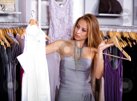 Gorgeous woman picking her choice stock photo, Portrait of a young lady picking her wardrobe in the cloth shop by Get4net