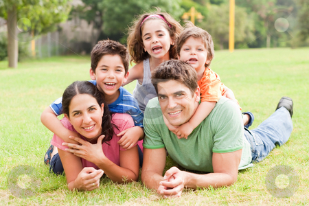 Happy family lying in the park stock photo, Happy family of five lying in the park and smiling at camera by Get4net