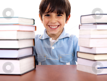 School boy surrounded by books stock photo, Smiling young school boy surrounded by books on white background by Get4net