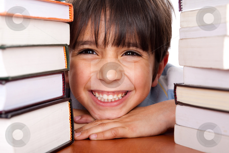 Close-up of young school kid stock photo, Young boy smiling at camera as he relaxes on table piled up with books by Get4net