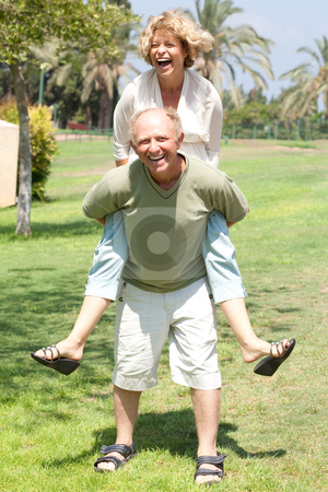 Image of Senior man giving woman piggyback ride stock photo, Happy active senior man giving woman piggyback ride by Get4net