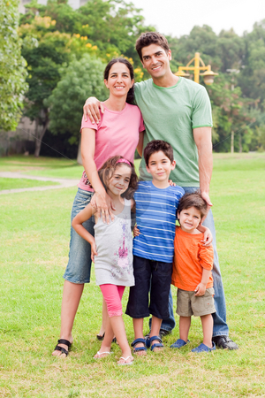 Middle aged couple standing with their children stock photo, Middle aged couple standing with their children, outdoors by Get4net