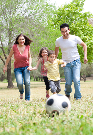 Parents and two young children playing soccer in the green field stock ...