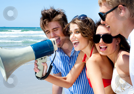 Teenagers shouting through megaphone stock photo, Happy young couples shouting through megaphone  on the beach in the summer by Get4net