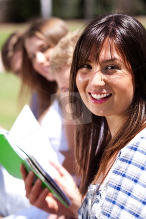 Smiling modern female student in focus stock photo, Smiling modern female student in focus with friends at the back by Get4net