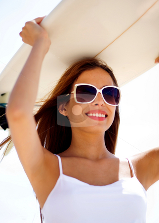 Smiling beach woman holding surfboard on her head stock photo, Close portrait of smiling beach woman holding surfboard on her head by Get4net 