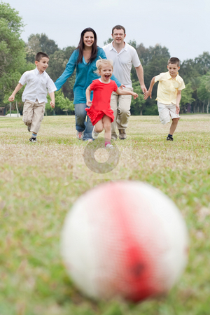 Happy family of five having outdoors and playing soccer stock photo, Happy family of five having outdoors and playing soccer running towards the football on natural background by Get4net