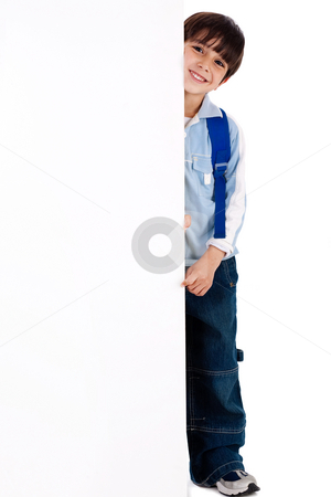 Young kid standing behind the board stock photo, Young kid standing behind the board on white isolated background by Get4net