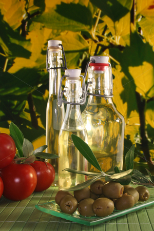Olive oil stock photo, Olive oil with olive branch and fresh olives and tomatoes by Marén Wischnewski