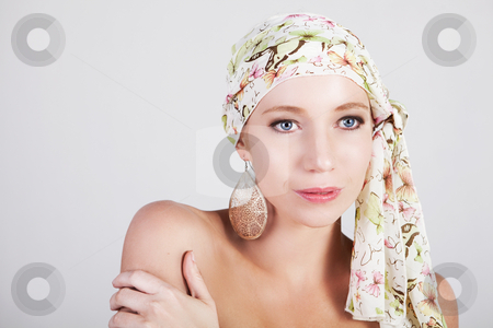 Beautiful Woman in a Colorful Headscarf stock photo, Head and shoulders portrait of an attractive young woman wearing a headscarf and ornate earrings. Horizontal shot. by Angela Hawkey