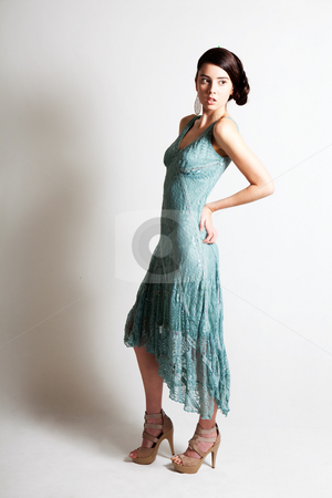 Beautiful Young Woman in an Elegant Evening Gown stock photo, A glamorous, high fashion woman looks off into the distance while posing in an elegant green dress and high-heeled shoes. Vertical shot. by Angela Hawkey