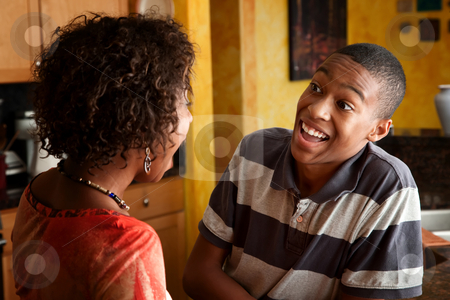African-American woman and teen laugh in kitchen stock photo, Attractive African-American woman and teen laugh in kitchen by Scott Griessel