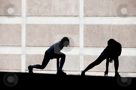 Two women stretching before running. stock photo, Two female friends stretching before a run. by Scott Griessel