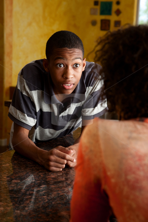 Surprised young African-American man stock photo, Surprised young African-American man talking to woman in kitchen by Scott Griessel