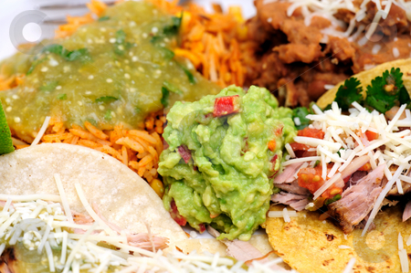 Carnitas With Rice And Refried Beans stock photo, Mexican style meal of Pork Carnitas soft tacos with refried beans, Spanish rice topped with fresh salsa verde and spicy guacamole. by Lynn Bendickson