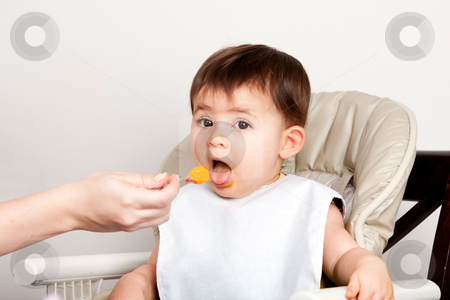 Happy baby spoon feeding stock photo, Beautiful happy baby infant boy girl with mouth open eating messy orange puree from spoon. by Paul Hakimata